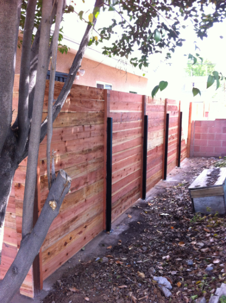 Contempory horizontal redwood fence using 5' steal posts